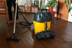 Kobiety czyści drewnianej podłoga z przemysłowym próżniowym cleaner zdjęcia stock