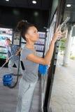 Kobiety czyści okno z squeegee przy fryzjerem obrazy stock