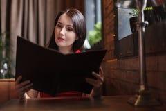 Kobiety czyta menu. Piękne w średnim wieku kobiety czyta menu przy Zdjęcie Royalty Free