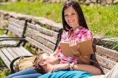 Kobiety czytania książka na ławki mężczyzna target205_0_ Zdjęcia Stock