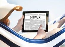 Kobiety czytelnicza gazeta na cyfrowej pastylce w hamaku Obraz Stock