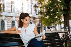 Kobiety czytelnicza gazeta podczas gdy siedzący na ławce Zdjęcie Stock