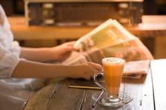 Kobiety czytelnicza gazeta z filiżanką kawy Zdjęcia Royalty Free