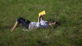 Kobiety czytelnicza książka kłaść na zielonym gazonie zdjęcie wideo