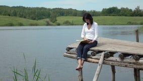 Kobiety czytelnicza książka na deskowym stołowym pobliskim jeziorze zbiory