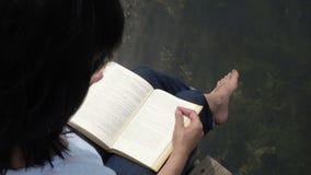 Kobiety czytelnicza książka na deskowym stołowym pobliskim jeziorze zbiory wideo