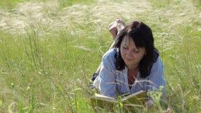 Kobiety czytelnicza książka na zielonym gazonie zbiory