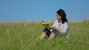 Kobiety czytelnicza książka na zielonym gazonie zbiory wideo