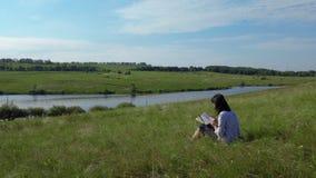 Kobiety czytelnicza książka na zielonym gazonie blisko jeziora zbiory wideo