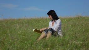 Kobiety czytelnicza książka wtedy kłaść w dół w trawie zbiory
