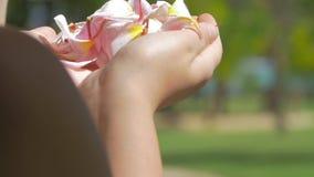 Kobiety dmuchania kwiatu płatki od ręk zdjęcie wideo