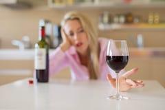 Kobiety dojechanie dla szkła wino podczas gdy samotnie w domu obrazy stock