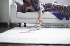 Kobiety dojechanie W kierunku Rozlewającego wina szkła Na dywaniku zdjęcie stock