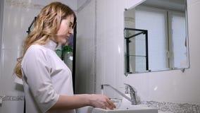Kobiety doktorski beautician w kontuszu nalewa wodę w wielkiego puchar myć twarz zbiory