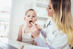 Kobiety doktorski egzamininuje dziecko z jęzoru depressor fotografia stock