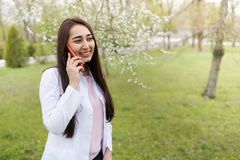 Kobiety doktorski m?wienie na telefonie kom?rkowym medycznego t?a kopii przestrze? outdoors szpital w kwiatu ogr?dzie Rozochoceni obrazy royalty free