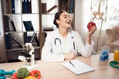 Kobiety doktorski obsiadanie przy biurkiem w biurze z mikroskopem i stetoskopem Kobieta trzyma czerwonego jabłka obraz stock