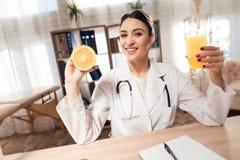 Kobiety doktorski obsiadanie przy biurkiem w biurze z mikroskopem i stetoskopem Kobieta trzyma pomarańcze i soku obrazy stock