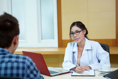 Kobiety doktorski opowiadać jej męski pacjent przy biurem Obraz Stock