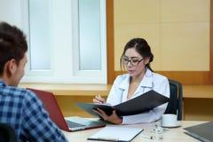 Kobiety doktorski opowiadać jej męski pacjent przy biurem Zdjęcie Royalty Free