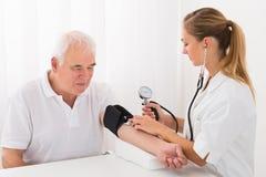 Kobiety Doktorski Sprawdza ciśnienie krwi Męski pacjent Obrazy Royalty Free