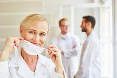 Kobiety doktorskiego kładzenia chirurgicznie maska dalej fotografia stock