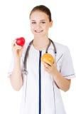 Kobiety doktorskiego mienia grapefruitowy i czerwony zdrowy serce. Obrazy Stock
