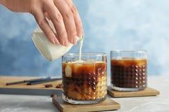 Kobiety dolewania mleko w szkło z zimną parzenie kawą obraz stock