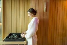 Kobiety dolewania woda na skałach w sauna Fotografia Stock