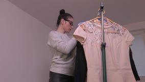 Kobiety dopatrywania bluzka blisko stojaka zdjęcie wideo