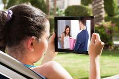 Kobiety dopatrywania film na cyfrowej pastylce zdjęcie stock