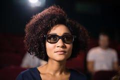 Kobiety dopatrywania film w theatre zdjęcia royalty free