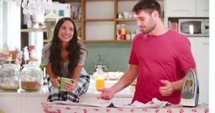 Kobiety dopatrywania mężczyzna prasowania koszula W kuchni zbiory wideo