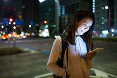 Kobiety dosłania telefon komórkowy przy nocą Zdjęcie Royalty Free
