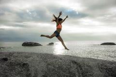Kobiety doskakiwanie na skale przy zmierzchem na Bakovern plaży, Kapsztad obrazy stock
