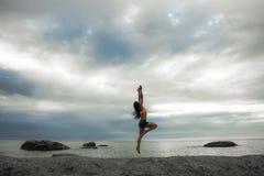 Kobiety doskakiwanie na skale przy zmierzchem na Bakovern plaży, Kapsztad obraz stock