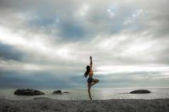 Kobiety doskakiwanie na skale przy zmierzchem na Bakovern plaży, Kapsztad zdjęcia stock