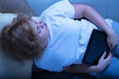 Kobiety dosypianie przy nocą z pastylka pecetem na kanapie zdjęcie stock