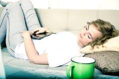 Kobiety dosypianie przy nocą z pastylka pecetem na kanapie obrazy stock