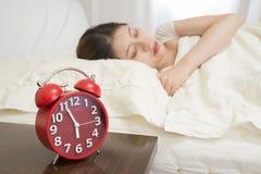 Kobiety dosypianie w łóżku obok budzika Fotografia Stock