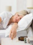 Kobiety dosypianie w łóżku z pigułkami w przedpolu Obrazy Royalty Free