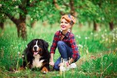 Kobiety dziewczyna z psim Bern w wiosna ogródzie Obraz Royalty Free
