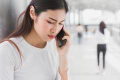 Kobiety dzwoni smartphone z poważny markotnym obraz stock
