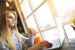 Kobiety freelancer sen coś relaksujący obsiadanie w kawiarni blisko wielkiego okno przy stołem z laptopem i glas Obrazy Royalty Free