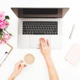 Kobiety freelancer używa laptopu i chwyta kawowego kubek Kobiet ręki, laptop, różowy róża bukiet, kawowy kubek i dzienniczek na b Zdjęcia Stock