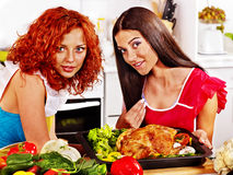 Kobiety gotuje kurczaka przy kuchnią. Zdjęcie Stock