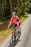 Kobiety halny jechać na rowerze w pogodny lasowy ono uśmiecha się Fotografia Royalty Free