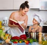 Kobiety i córki narządzanie karmowy konsultujący książkę kucharska Zdjęcia Royalty Free