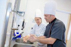 Kobiety i mężczyzna domycia ręki przy kuchennym zlew zdjęcia stock