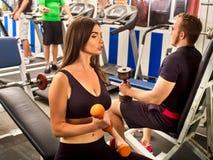 Kobiety i mężczyzna mienia dumbbell trening przy gym Przyjaciół mężczyzna Obraz Royalty Free